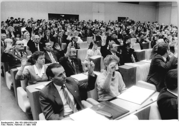 Bundesarchiv, Bild 183-1989-0303-029 / Reiche, Hartmut / CC-BY-SA 3.0 ADN-ZB Reiche 3.3.1989 Berlin: Tagung der Volkskammer Die Volkskammer der DDR beschloß auf ihrer 8. Tagung das aktive und passive Wahlrecht für ausländische Bürger zu Kommunalwahlen in der DDR. Einstimmig billigten die Abgeordneten ein entsprechendes Ergänzungsgesetz zum Gesetz über die Wahlen zu den Volksvertretungen der Deutschen Demokratischen Republik.